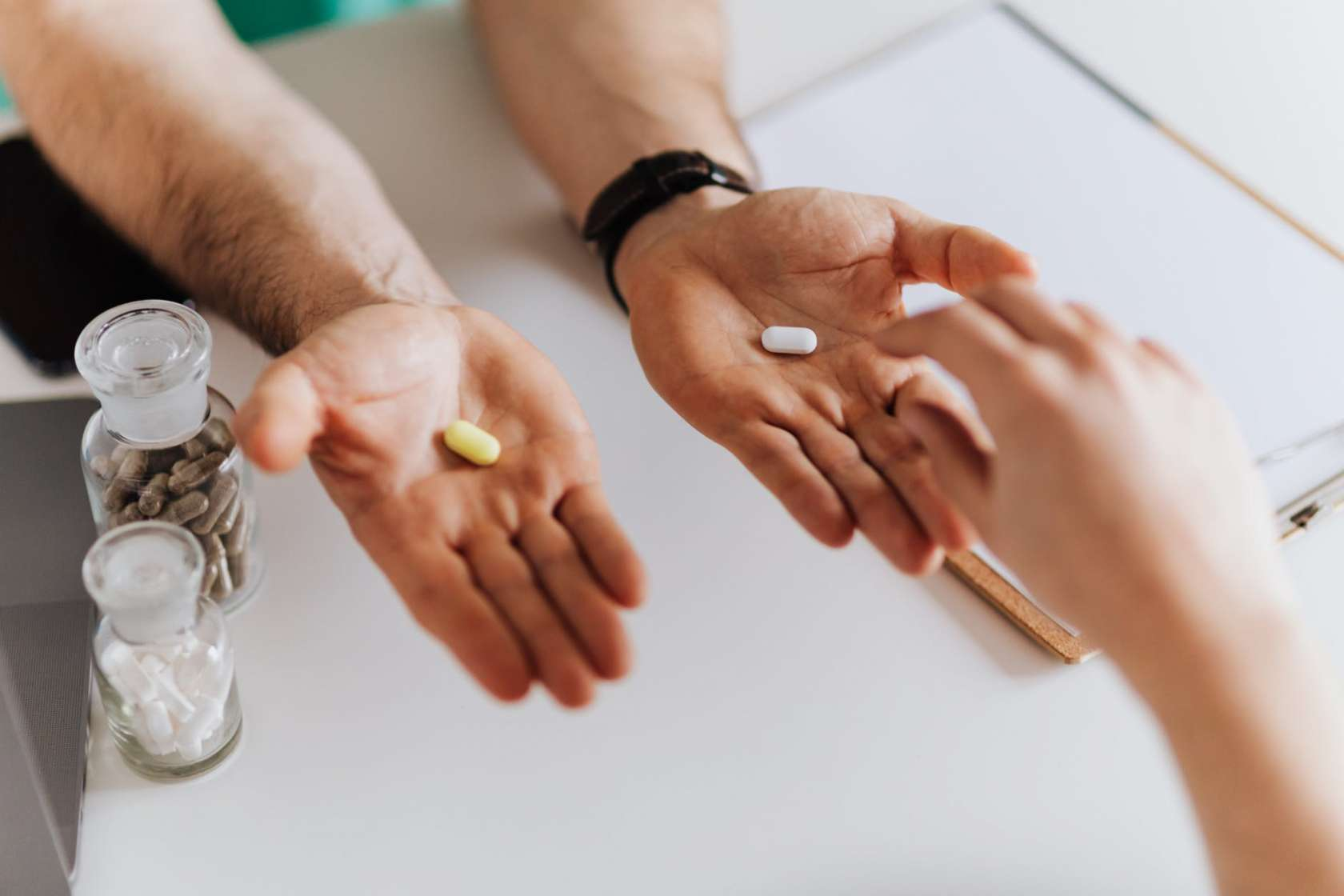 Person grabbing pill fro right hand of healthcare professional